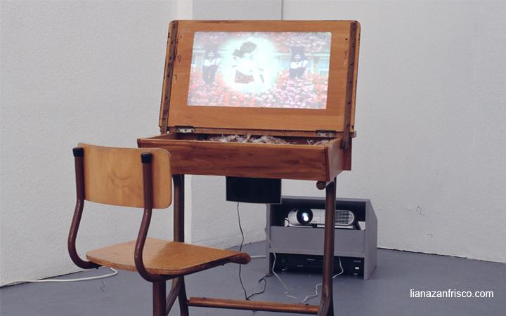 Video-scultura un banco di scuola con il piano ribaltato sul quale viene proiettato il video.