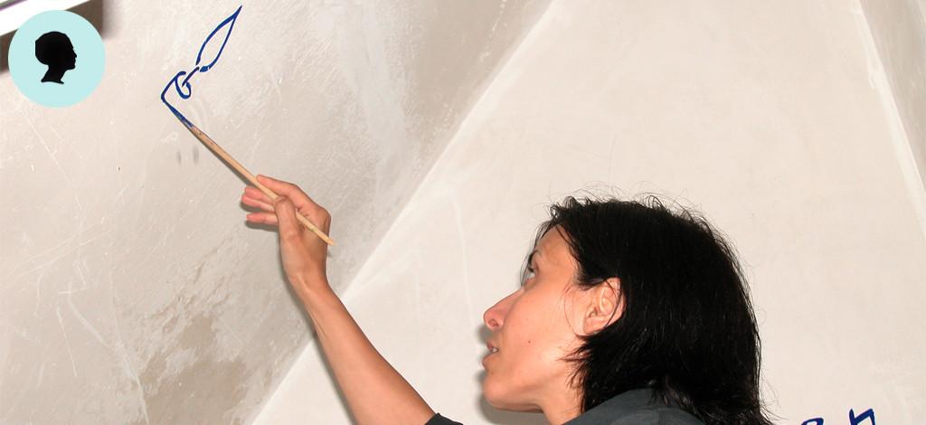 L'artista dipinge una candela sulla parete di un appartamento privato