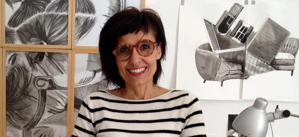 Un disegno al giorno. Liana Zanfrisco in primo piano, capelli neri, occhiali, maglioncino a righe bianco e nero. Sulla parete alle spalle , i suoi disegni.